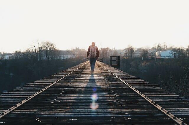 man loopt depressief over treinrails