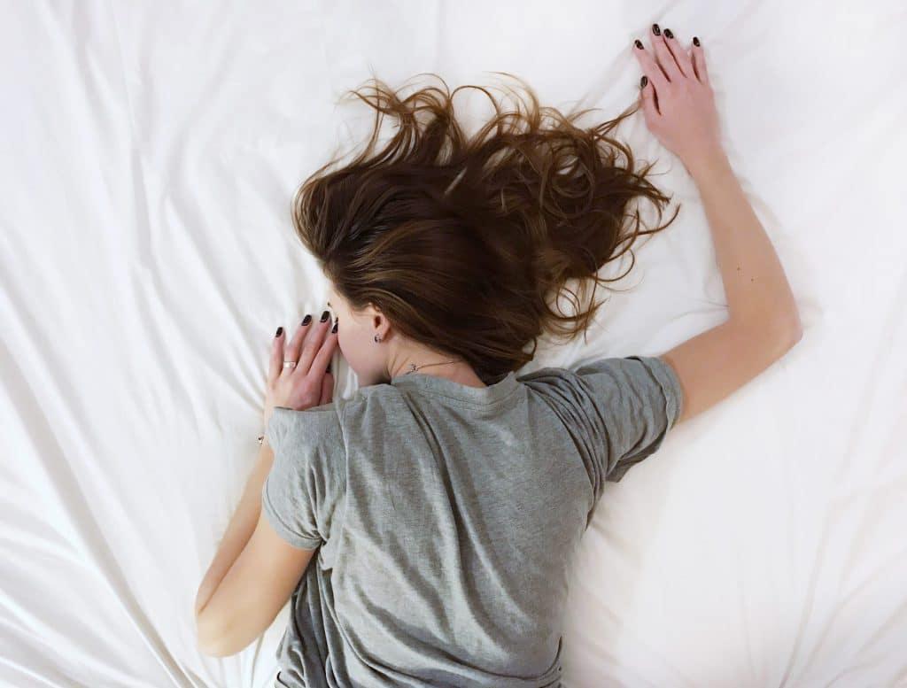 Vrouw ligt vermoeid in bed