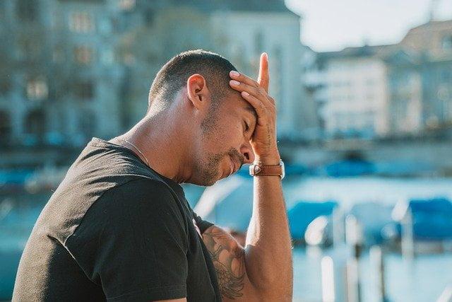 Jonge man met hoofdpijn en hand op voorhoofd