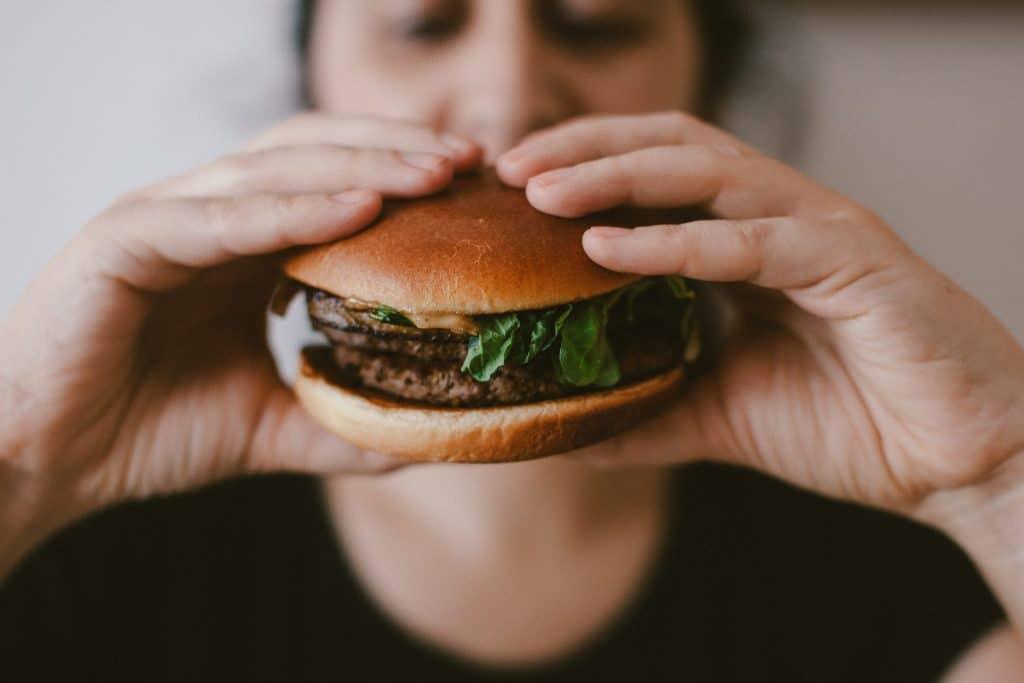 gestreste man eet hamburger
