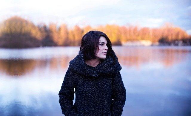 Vrouw staat in de natuur en worstelt met negatieve gedachtes