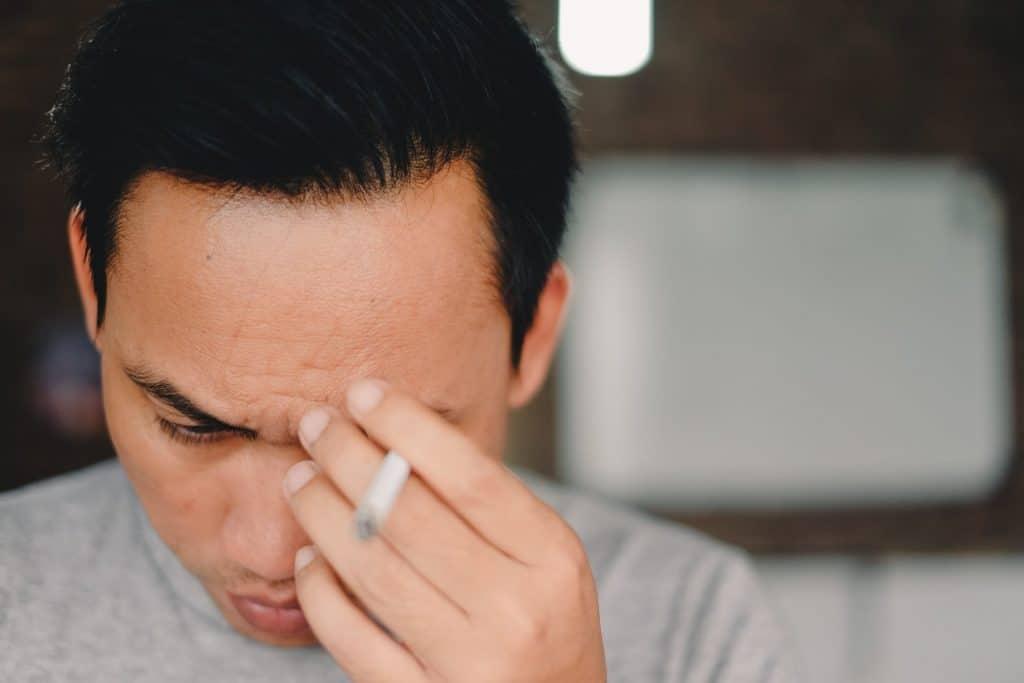 Man is gestresst en rookt een sigaret