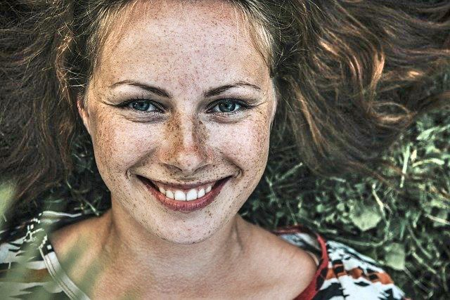 Veerkracht: vrouw ligt lachend in gras zonder stress