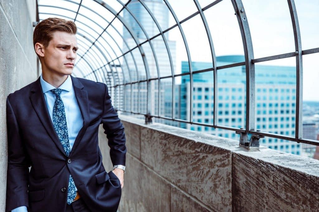 Zakenman met chronische stress kijkt uit op kantoren