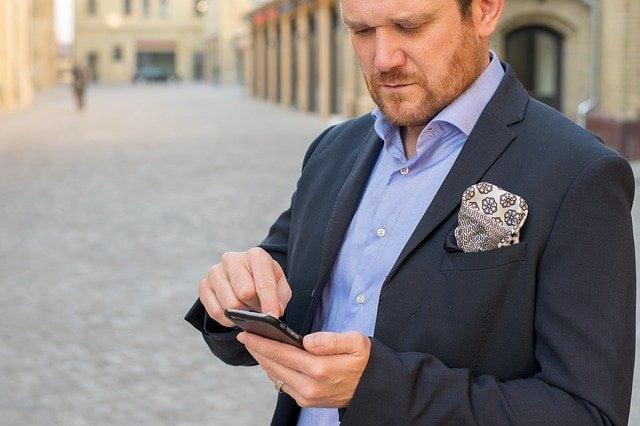 Man overspannen met telefoon in hand