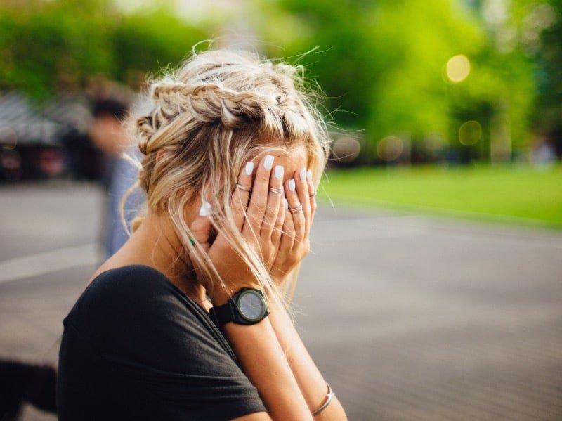 Hoog cortisolgehalte: Vrouw zit met handen voor gezicht
