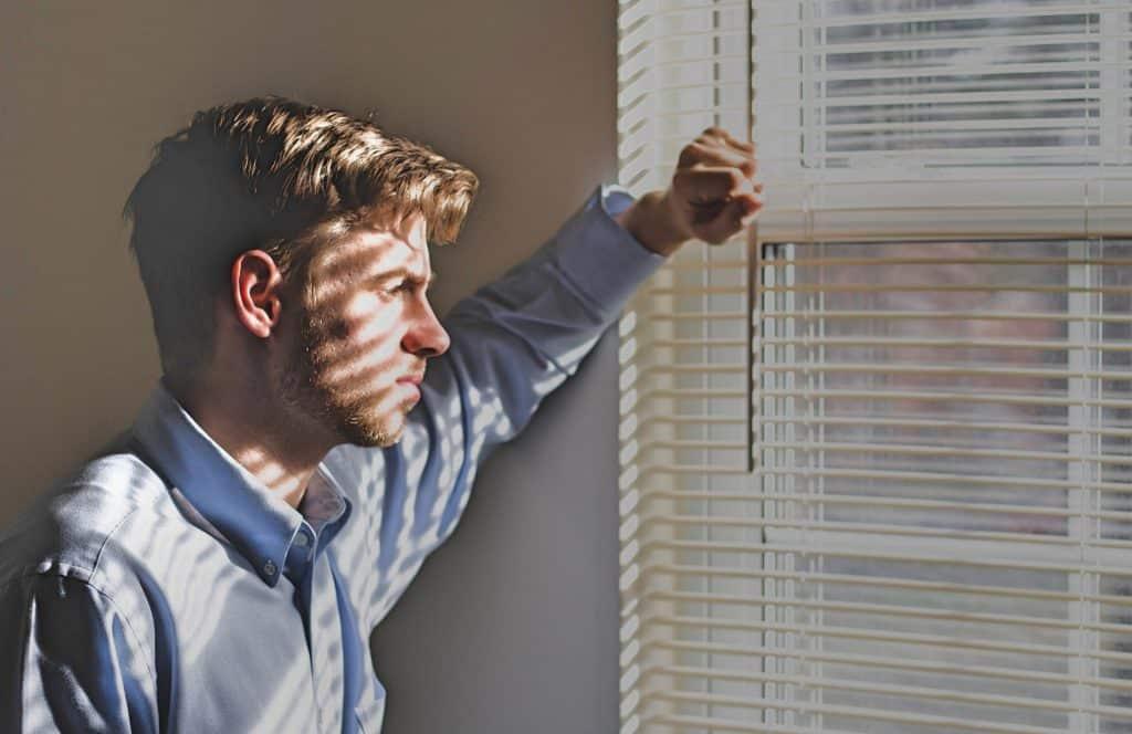 Man met stress staart uit het raam