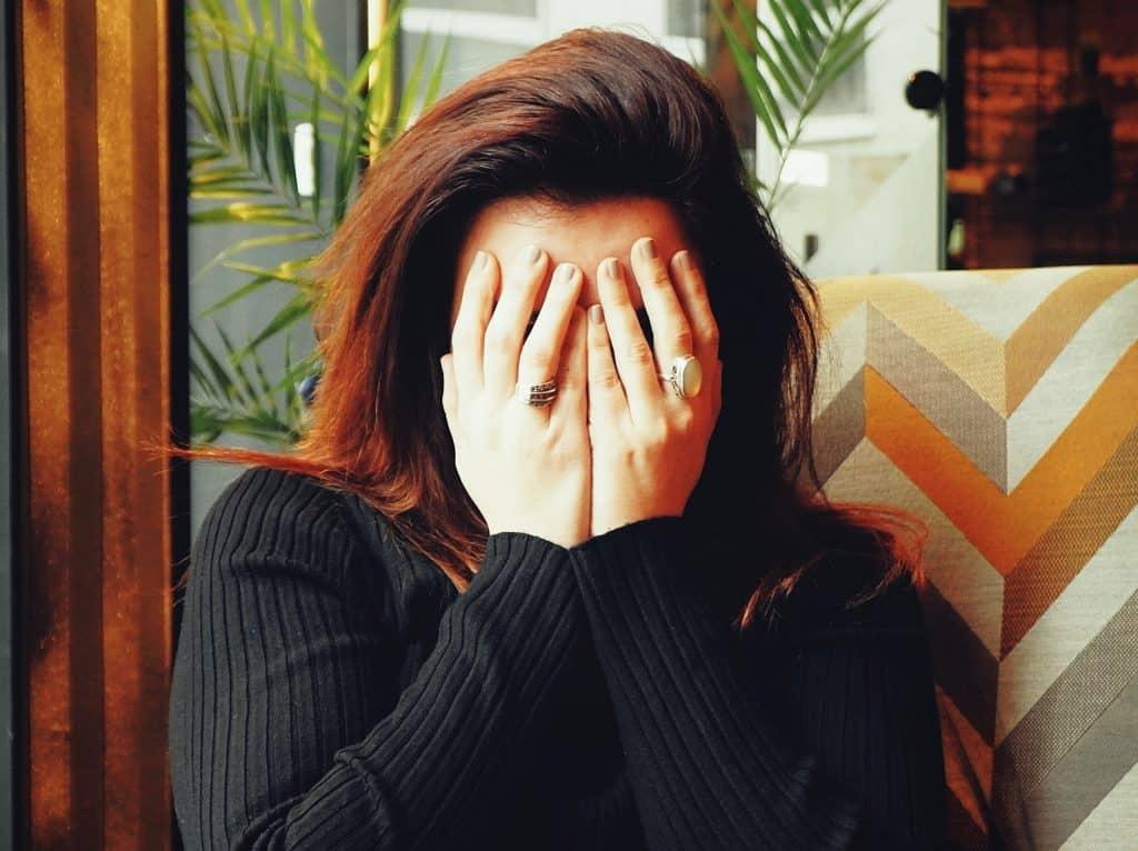 Vrouw met stress slaat handen voor het gezicht
