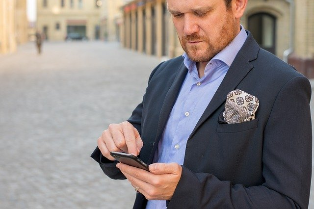 zakenman leest op zijn telefoon