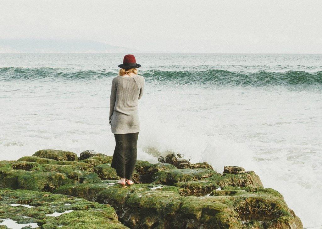 Vrouw staart uitzichtloos naar de zee