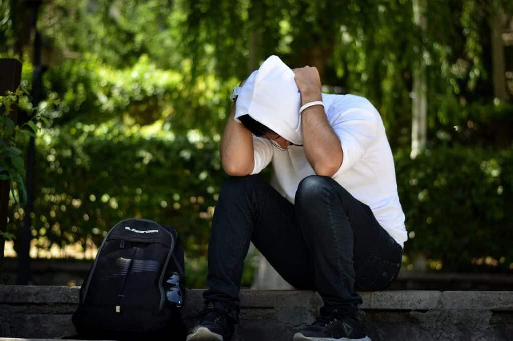 gestreste man zit op stoep
